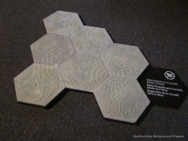 A display of white hexagonal floor tiles with designs in them