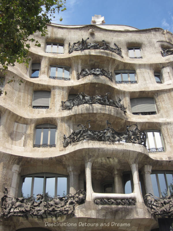 Balconies on the stone Casa Milà building with exquisite ironwork railings