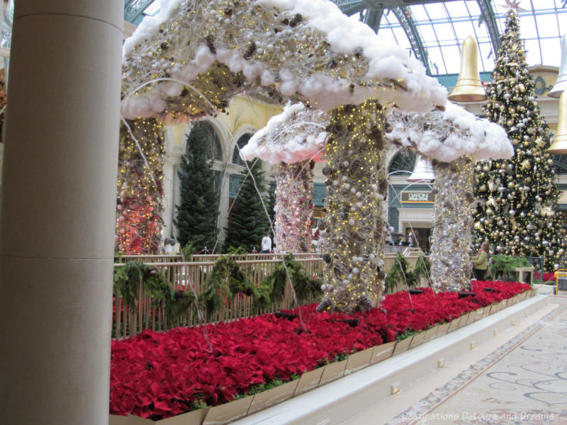 A bed of red poinsettias, columns covered in gold and white balls and lights holding up a roof of the same balls and lights trimmed with white to look like snow in a Christmas display in Bellagio Hotel