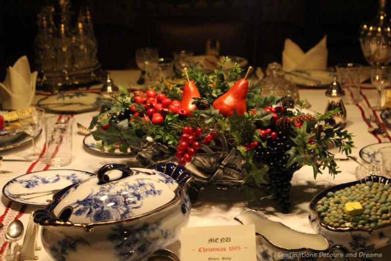 Victorian-era Christmas table with centerpiece of greenery, red berries, and red pears.