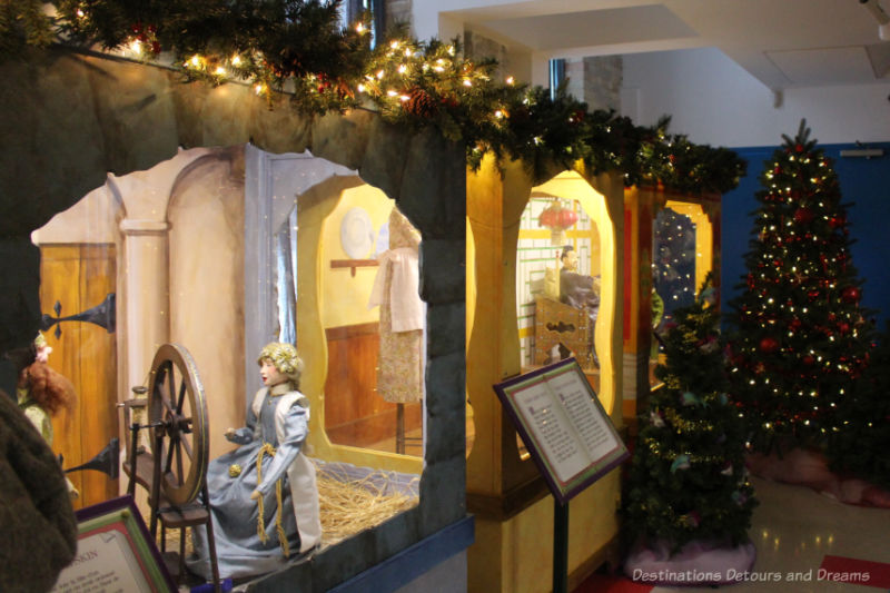 Fairytale vignettes in display cases (spinning girl from Rumpelstiltskin featured in foreground) as part of a Christmas display