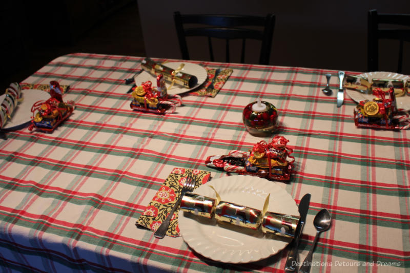 Table set for Christmas dinner with red, green, and white table cloth, white plates, Christmas crackers, mini-sleights of candies