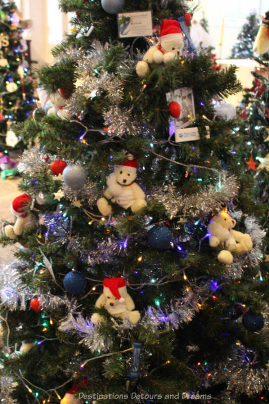A Christmas tree decorated with a silver garland and little white teddy bear with red hat ornaments