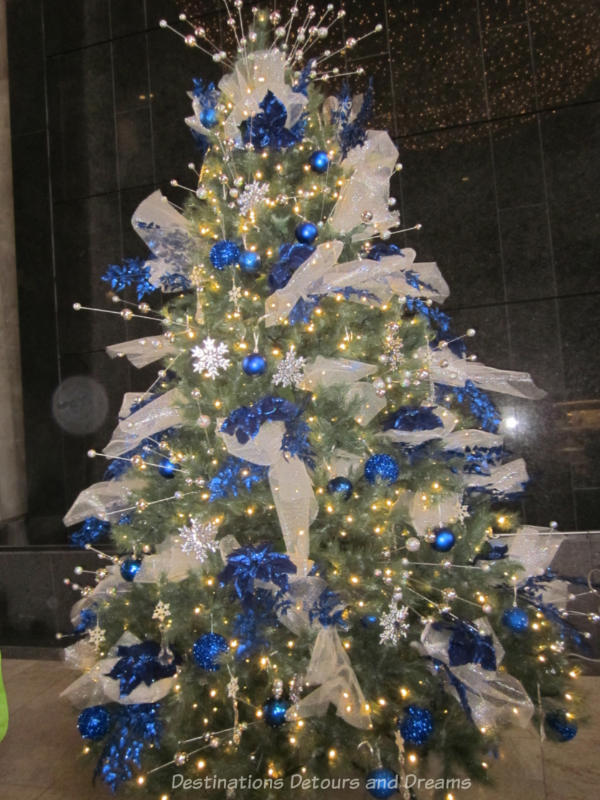 Christmas tree decorated with sheer white bows, sparkly white snowflakes, blue balls, and blue garlands