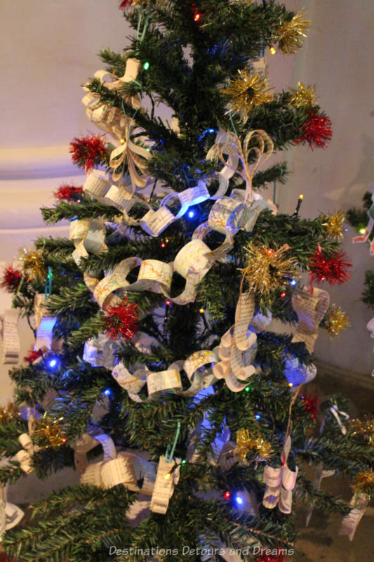 A Christmas tree decorated with paper chain garlands and red tinsel balls
