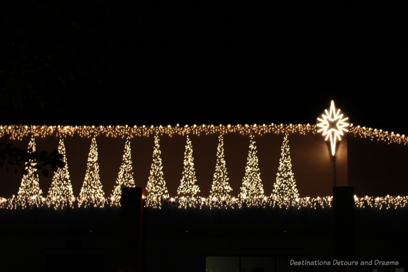 White lights decorating the top of a building with shapes ofr Christmas trees and a giant star