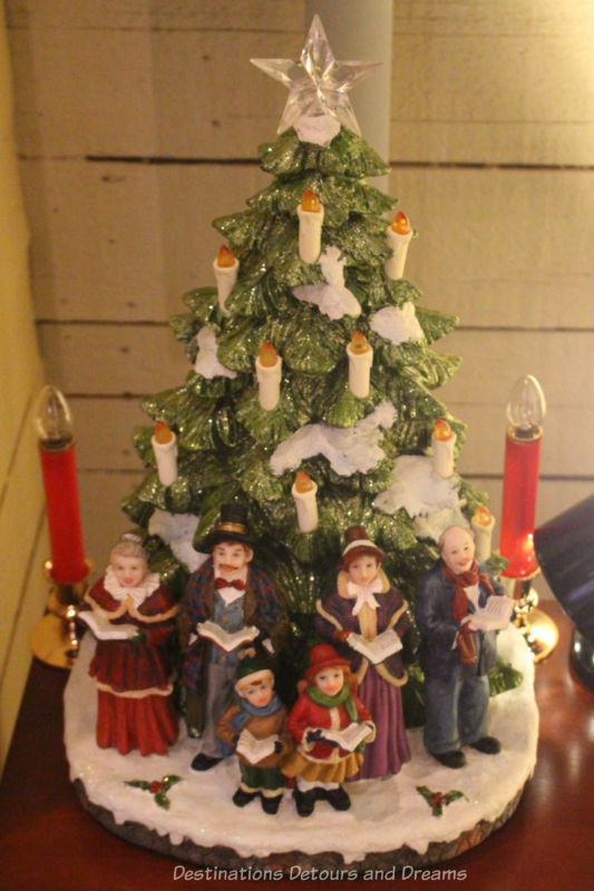 Ceramic Christmas tree with candle lights and carols in front of it