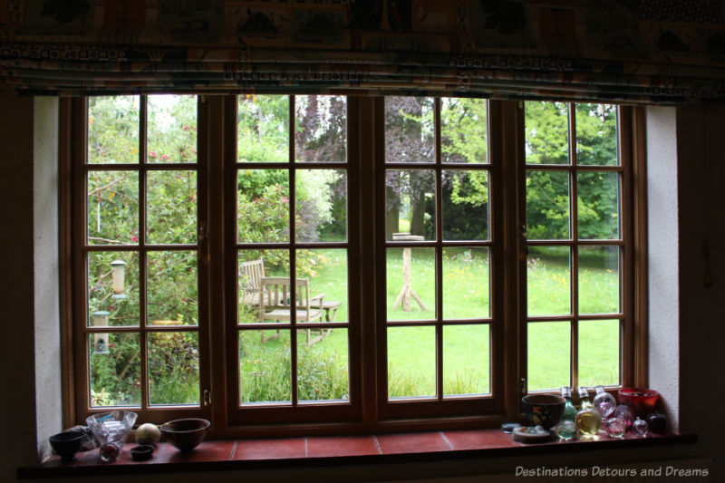 Lattice-paned window looking onto green lawn and trees of an English garden
