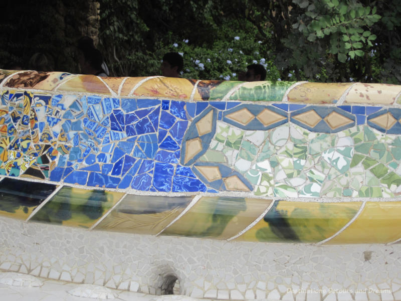 Stone bench with colourful tile mosaics on its back at Park Güell