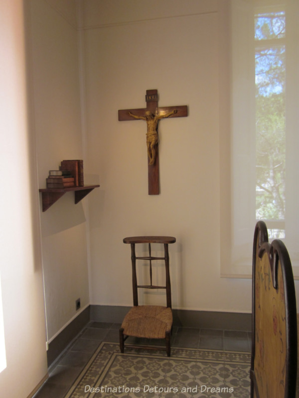 Austere wood chair with cane seat under a crucifix as part of room's prayer area