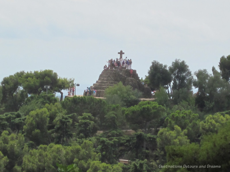 A cross monument atop a hill at Park Guell
