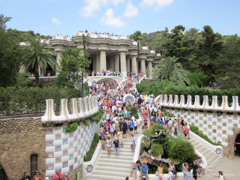 Staircase with mosaic walls in a park leading to a columned covered pavilion at Park Güell
