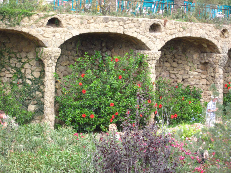 Flowers and foliage against a stone wall at Park Güell