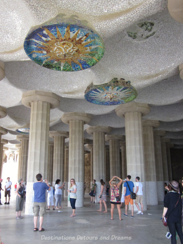 A patio-style area with large columns holding up an undulating ceiling decorated with mosaic disks
