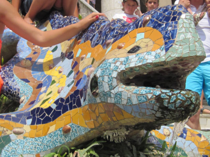 Figure of a dragon or salamander covered in a colouful mosaic of tiles at Park Güell