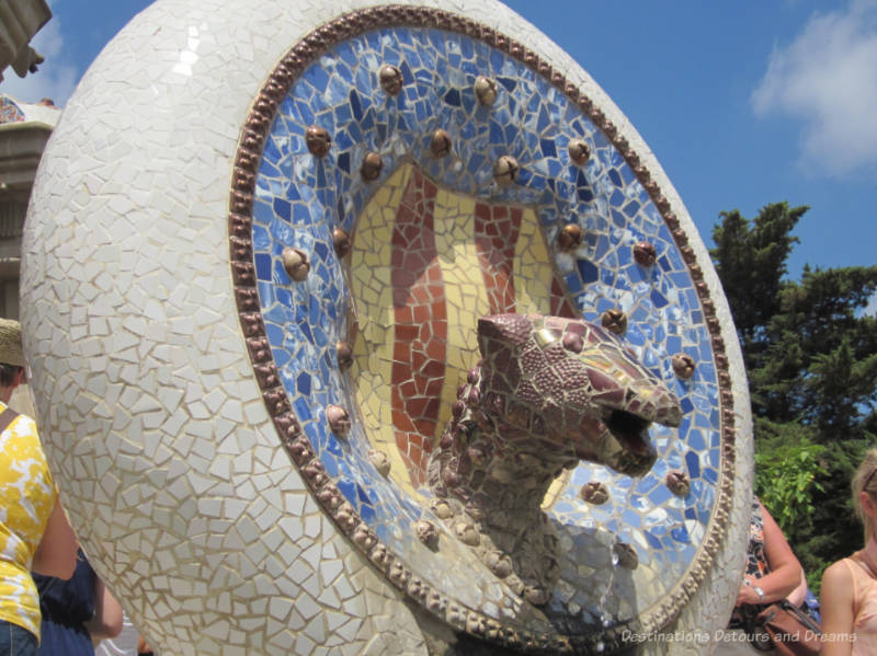 Mosaic tile head in a circle on stairway at Park Güell