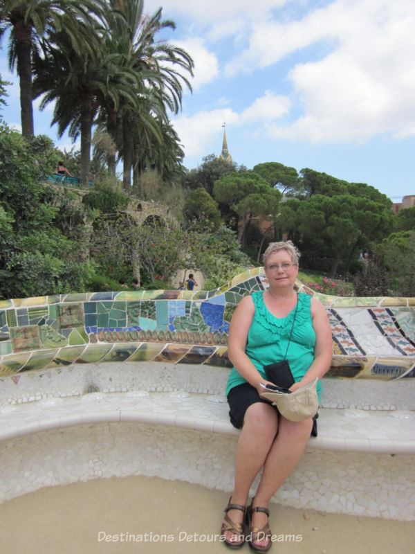 Sitting along a curved bench decorated with mosaic tiles at Park Guell