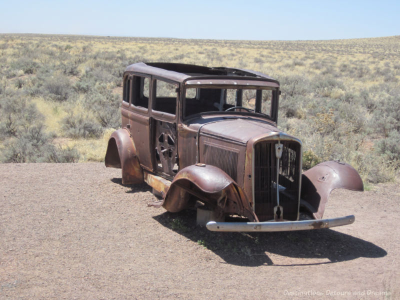 Old rusted car missing tires and doors sitting a gravel pull-out in the badlands of Petrified Forest National Park