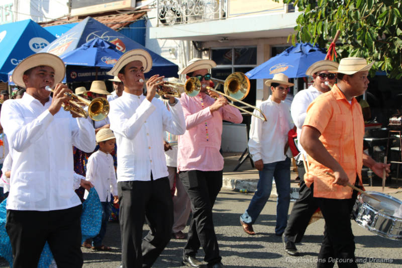 A band of men dressed in traditional Panamanian attire marching and playing in the Thousand Polleras Parade