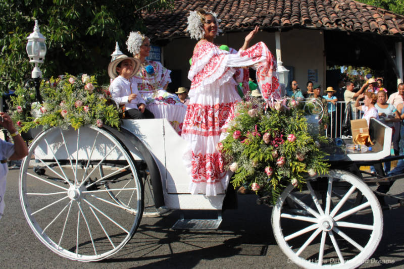 Woman in a white and red pollera dress riding in an open white carriage