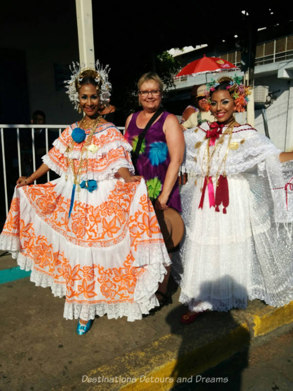 Blog author with two women clad in traditional Panamanian polleras at the Thousand Polleras Parade