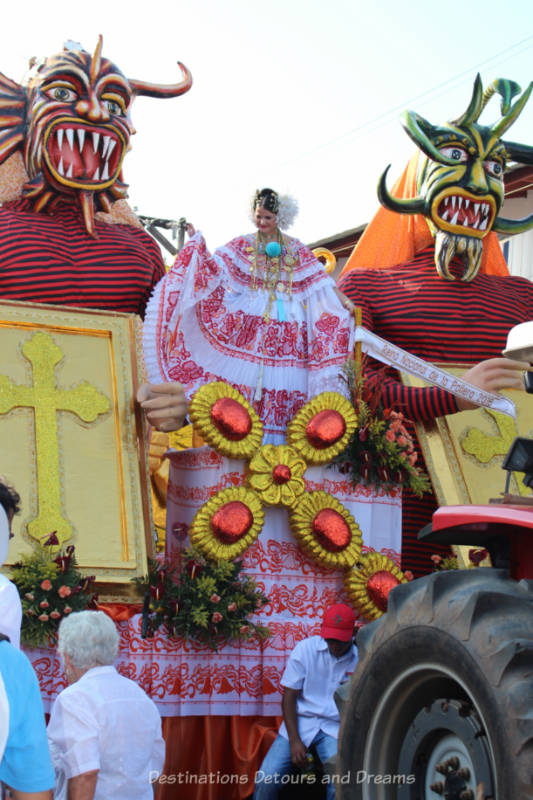 Parade float featuring devil mask characters flanking a woman in a red and white pollera dress