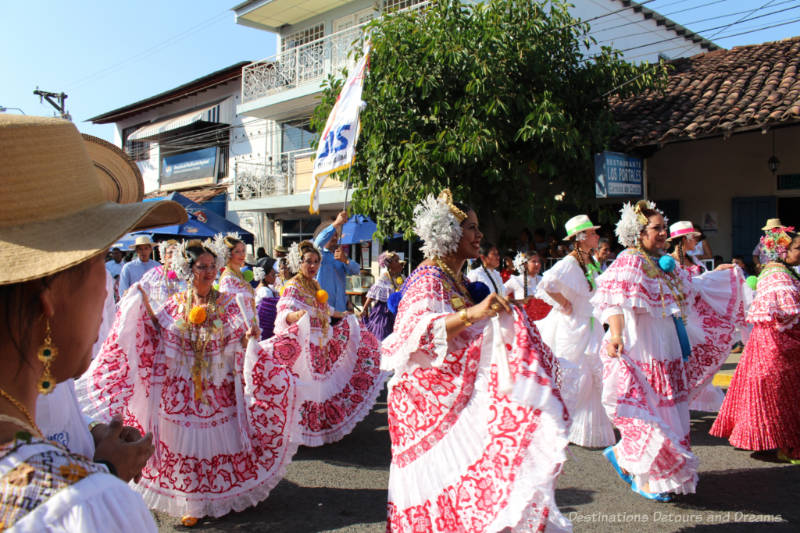 Several women clad in white and red polleras dance through the street in the Thousand Polleras Parade