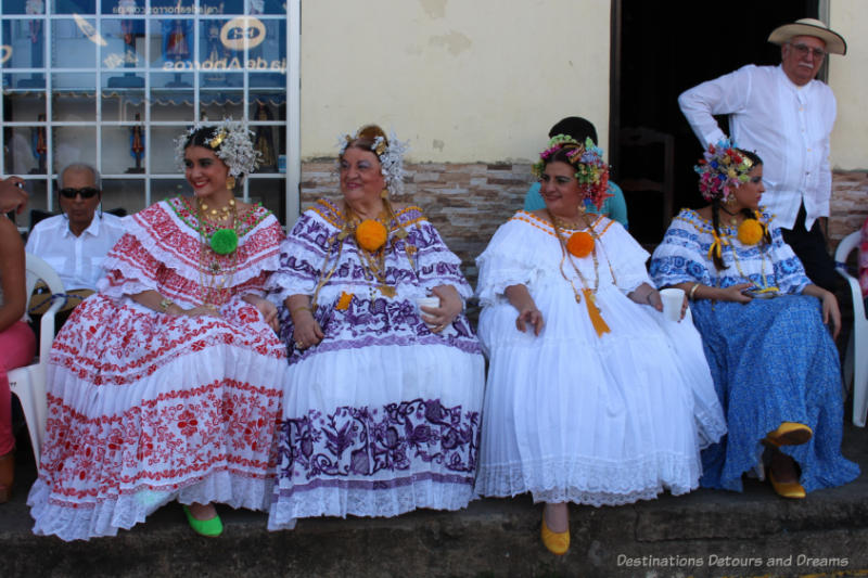 Four women in traditional Panamanian polleras seated and waiting for the Thousand Polleras Parade