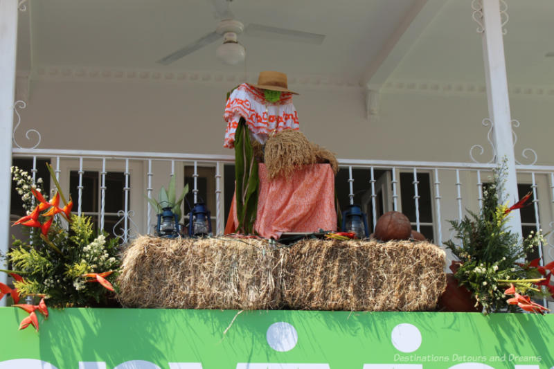 Decorations on the second level balcony of building in Las Tablas, Panama featuring a seated woman in traditional dress on a bale of hay flanked by floral bouquets