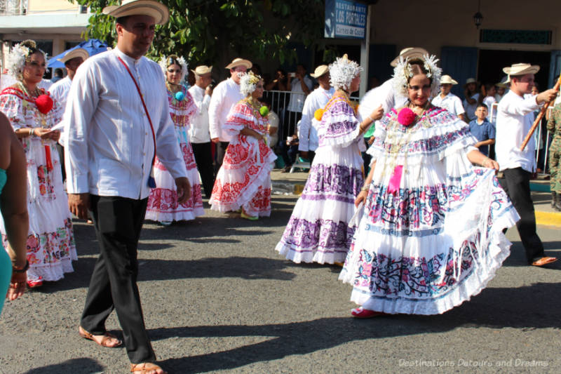 Women in pollera dresses and men in traditional attire parading in Las Tablas, Panama in the Parade of a Thousand Polleras