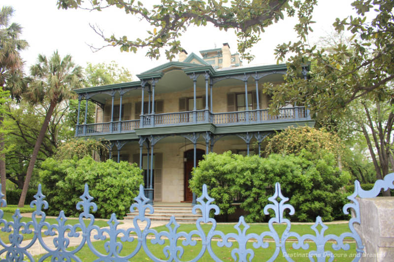 Two-story heritage home with cast iron porch and fence decorations