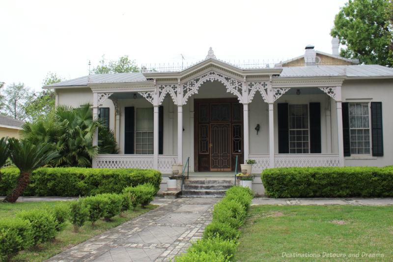 Heritage home in San Antonio King William District with intricate front veranda latticework detailing