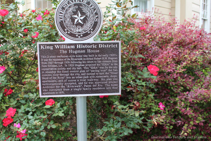 History signage amid flowery shrubs in King William Heritage District in San Antonio