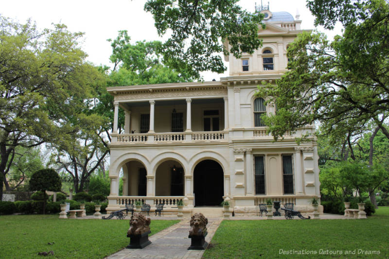 Elaborate two story heritage mansion with veranda and a three-story tower attached on the right