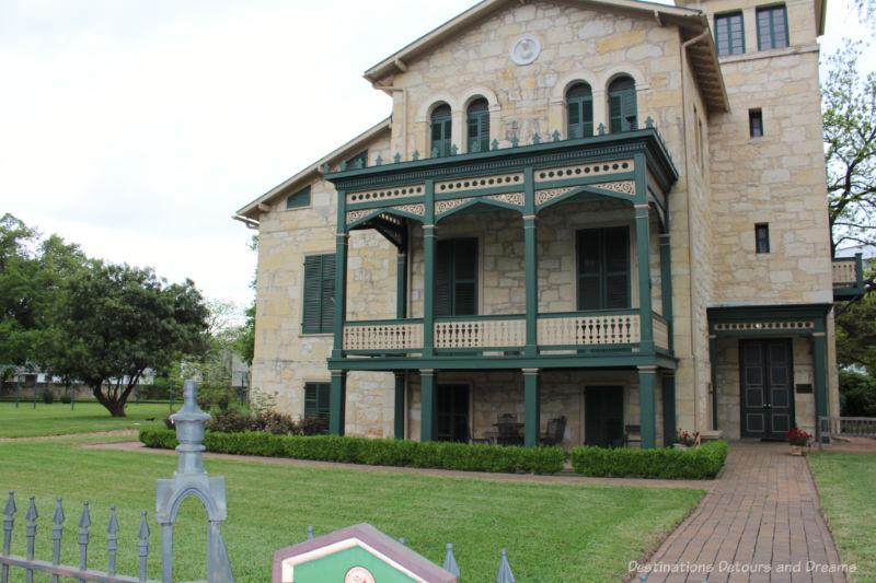Three story brick heritage home with green trim verandas in San Antonio King William district
