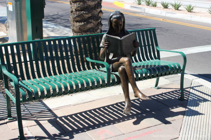Sculpture of a sitting woman reading a book. She sits on a real park bench.
