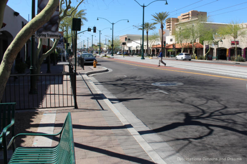 Wide main street of downtown Mesa, Arizona lined with low-rise buildings and with light rail system running through middle.
