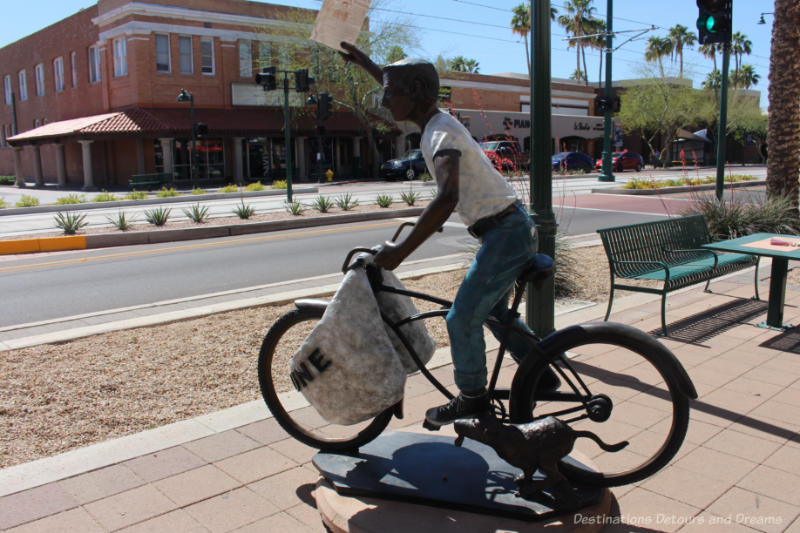 Sculpture of a newspaper delivery boy on a bicycle