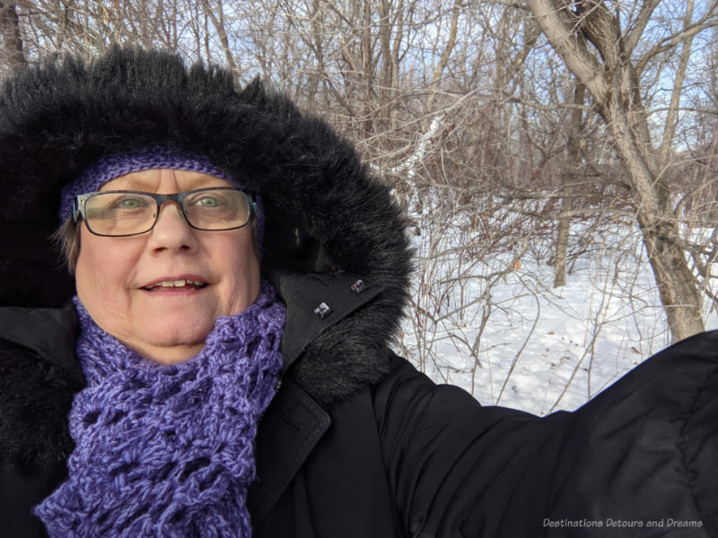 Woman in black parka and purple scarf in front of snow and trees