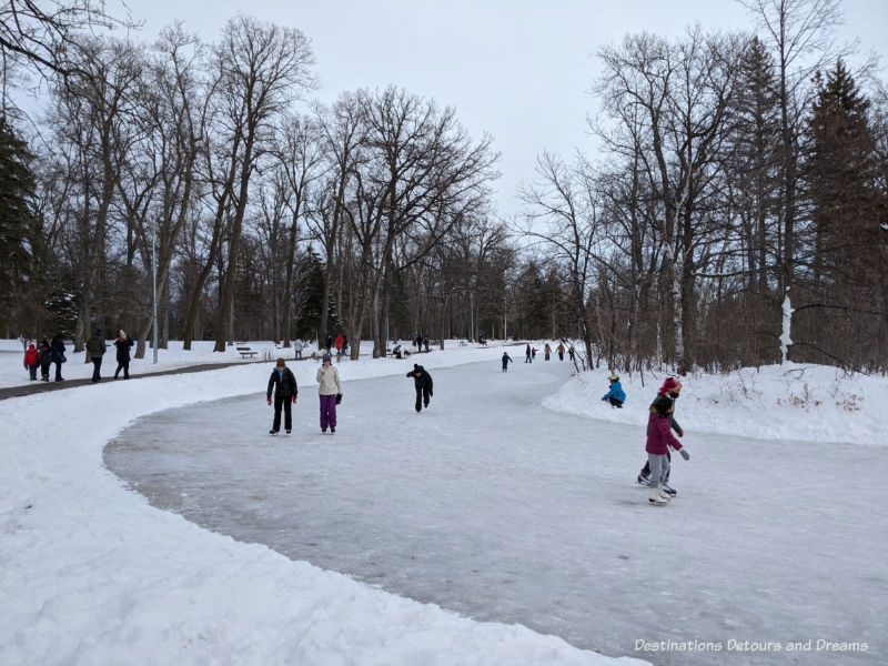 Skaters on a frozen park and people walking the path around the pond in a treed park