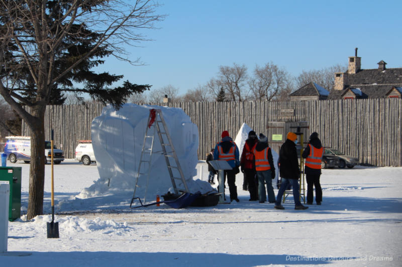 Group of snow carvers and workers around an snow sculpture