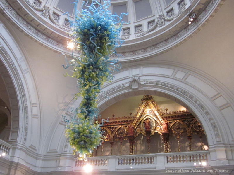 Chandelier of green and blue glass balls and spikes by Dale Chihuly hanging in entrance of Victoria and Albert Museum