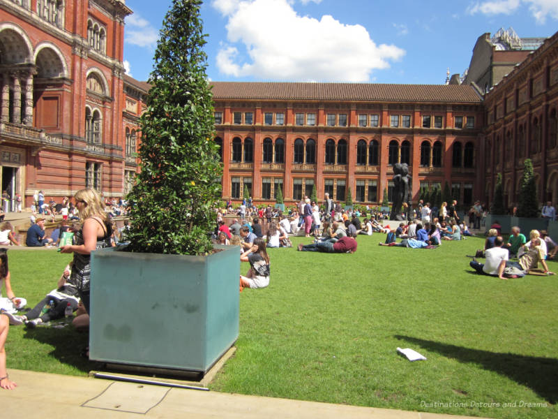 People sitting on the lawn of the V&A courtyard with the beautfiul red stone walls of the museum surrounding them