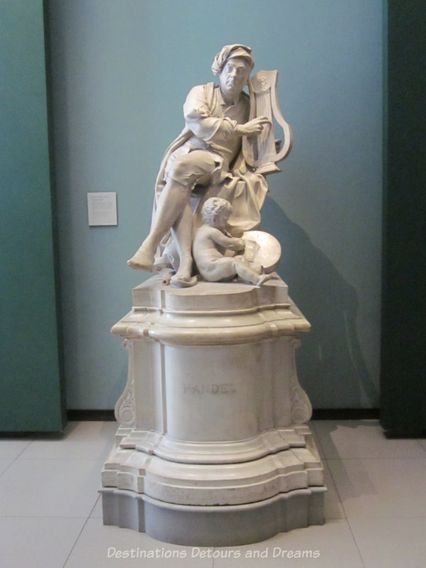 Marble sculpture of Handel playing lyre while a cherub at his feet transcribes