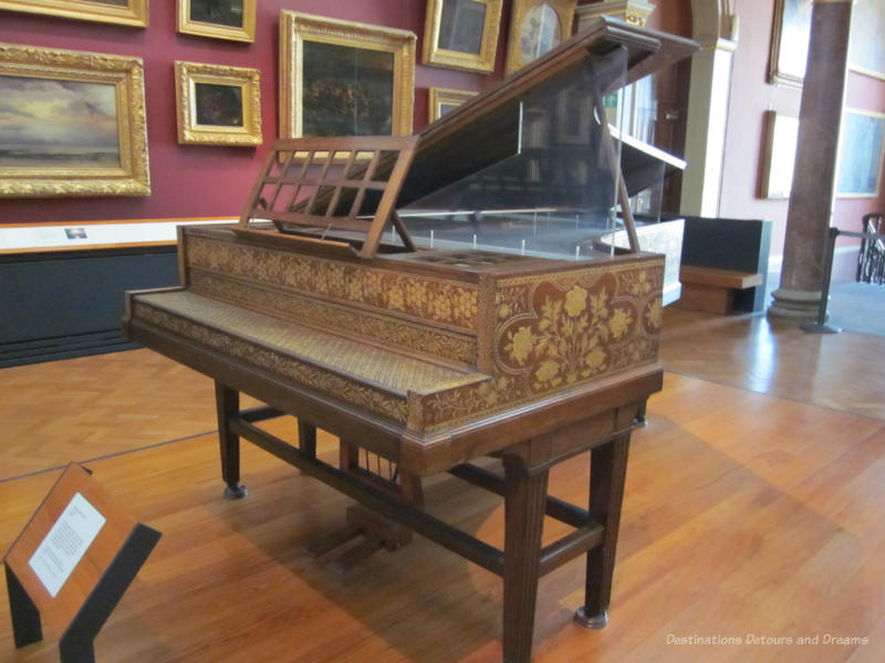 19th century grand piano with gold-coloured flower design covering the wood