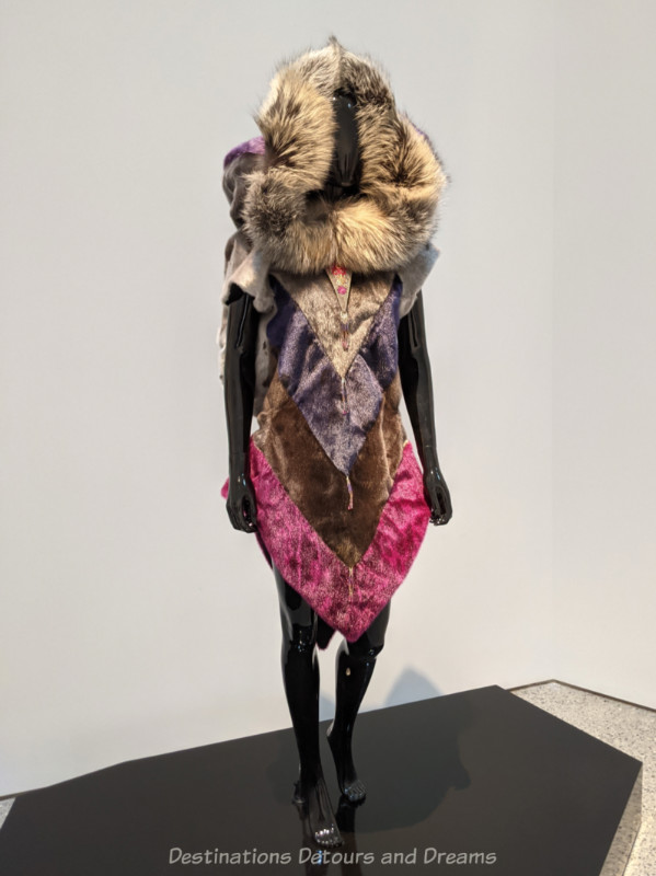 Inuit art piece: dyed sealskin coat with v-shaped stripes of pink, browns, and purple with a fox fur hood