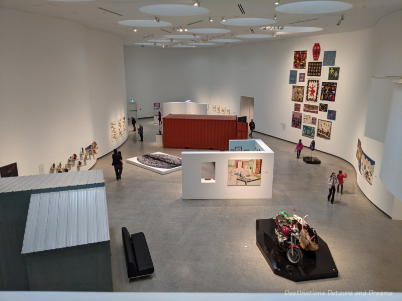 Large sky-lit  two-story white-walled gallery displaying Inuit art of the INUA exhibition, inaugural exhibition of Qaumajuq