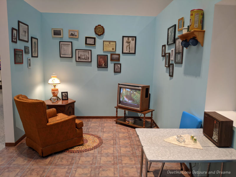 Recreation of a 1970s era living space with easy chair, television, chrome table at an Inuit art exhibit