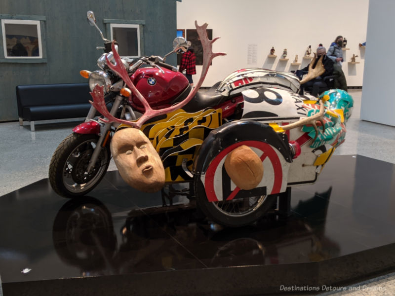 Inuit art piece featuring a motorcycle covered with other pieces such as antlers, a wood sculpted face, and more