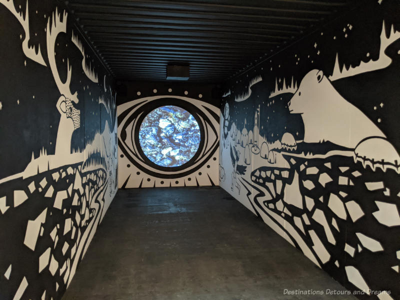 Inside of a shipping container painted with a black background and white images of a northern scene by Inuit artist Glenn Gear